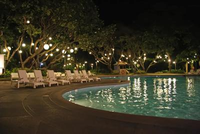 Concrete pool deck with cute lounge chairs over looking pool at night