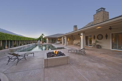 Decorative concrete pool deck and patio with lounge chairs and modern built in fire pit